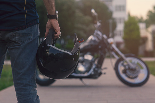 rear view of a man holding a helmet by his side with a motorcycle parked in the background