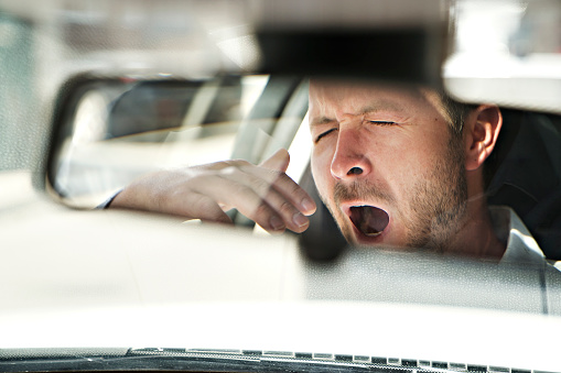 reflection of a man in a rear-view mirror yawning in his car because is so tired