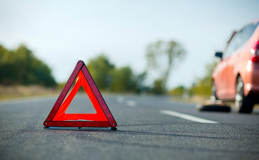 Red triangle and a disabled/broken car on the side of the road